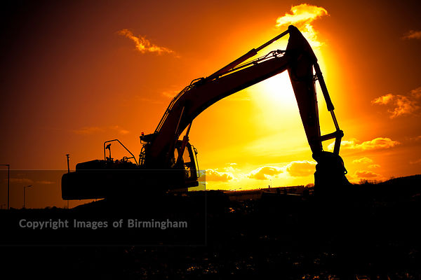 A digger in silhouette on a construction site