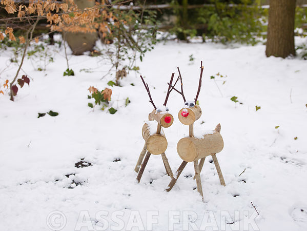 Wood Deer figurines with Christmas tree in snow