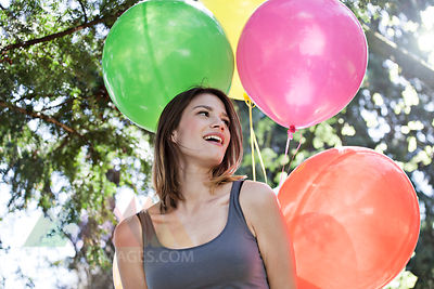 Germany, Cologne, Young woman with balloons, smiling