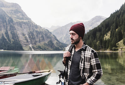 Austria, Tyrol, Alps, serious man at mountain lake