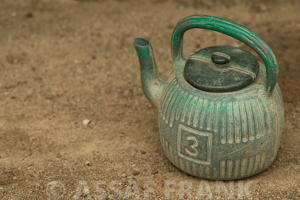 Africa, Nigeria,  Close-up of a teapot on sand