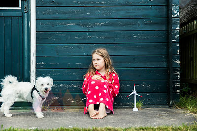 Girl wearing bathrobe outdoors sitting at wooden hut with toy wind turbine and dog