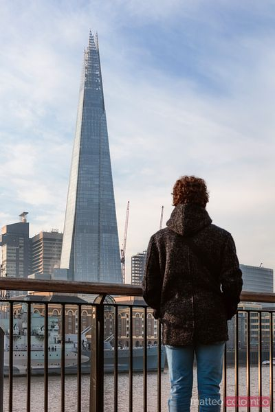 Young man standing in front of the Shard, London