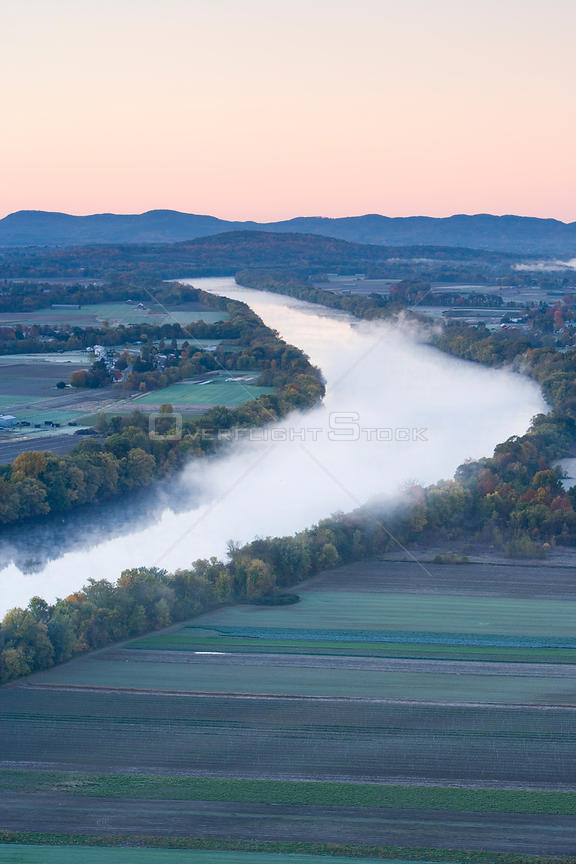 Aerial view of mist rising from the Connecticut River at dawn as seen from South Sugarloaf Mountain in the Sugarloaf Mountain...
