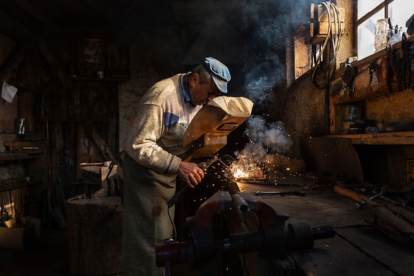 Portrait of a Blacksmith using a Welder in his Forge