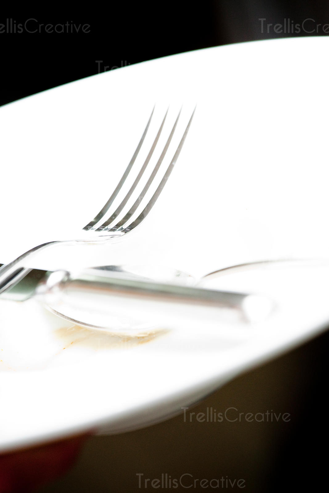 Shiny fork and knife on a white dinner plate