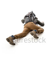 A Figurestock image of a man climbing or crawling, in outdoor gear – shot from a different perspective