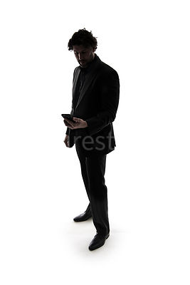 A mystery man, in a suit, checking a mobile phone, in silhouette – shot from eye level.