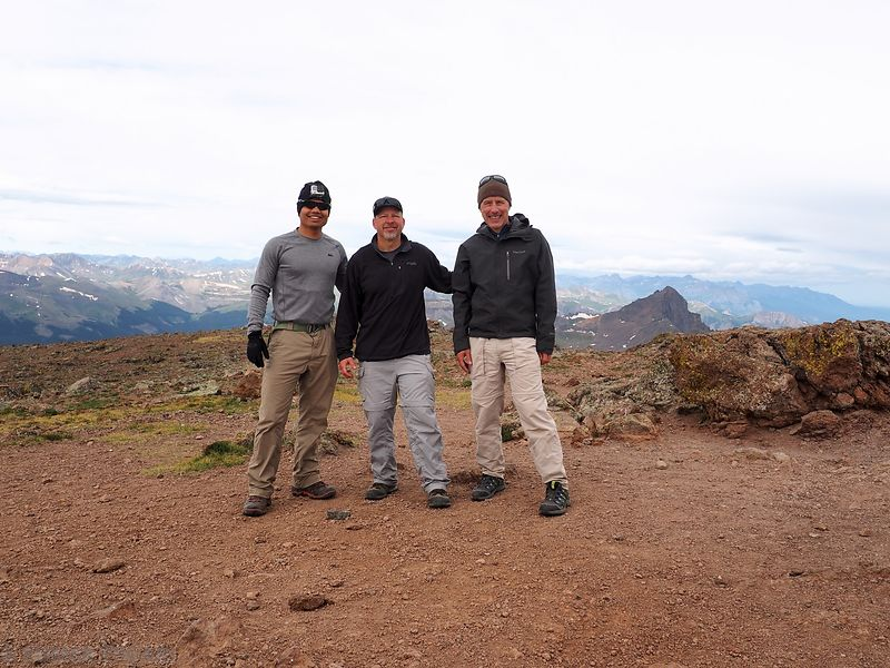 A group photo on the summit of Uncompahgre Peak. Wetterhorn Peak is visible in the background