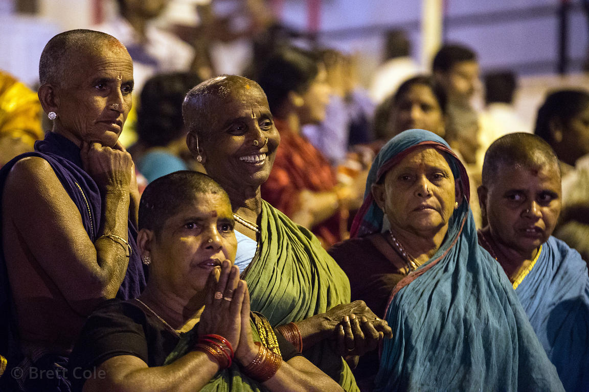 Women Hindu pilgrims with shaved heads pray during Ganga Aarti along the Ganges River, Dashashwamedh Ghat, Varanasi, India