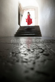 An atmospheric image of a blurred woman, in a red dress, walking down some steps into in an old room.