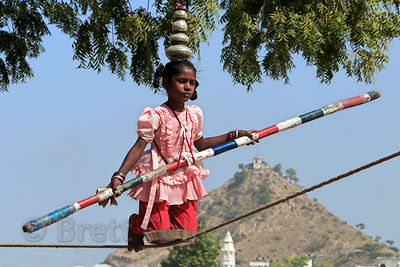 A girl does a slack wire routine at a carnival, with Gayatri temple in the background, Pushkar, Rajasthan, India