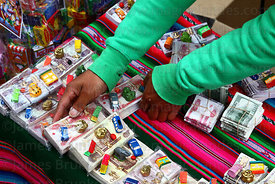 Girl arranging bundles of miniature bank notes on her stall at Alasitas festival, La Paz, Bolivia
