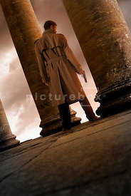 An atmospheric image of a mystery man with a gun, standing looking out of an old temple.
