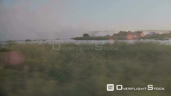 Aerial wide angle lens flare side view of flowing river with vegetation on riverbank and in middle of river to lip of waterfa...