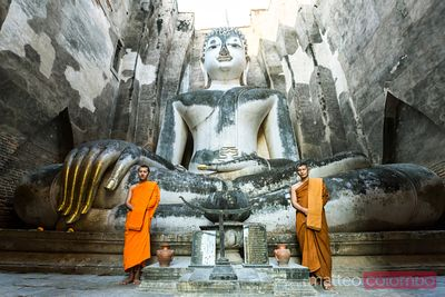Thailand, Sukhothai. Buddhist monks in front of Giant Buddha