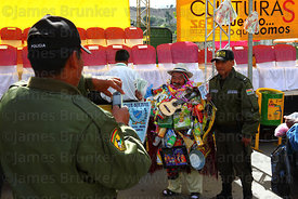 A policeman has his photo taken with Ricardo Paco (the official ekeko) at the Alasitas festival, La Paz, Bolivia