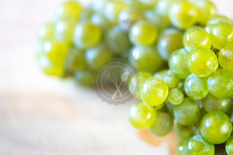 bunch of green grapes on light coloured wooden board with text space on left