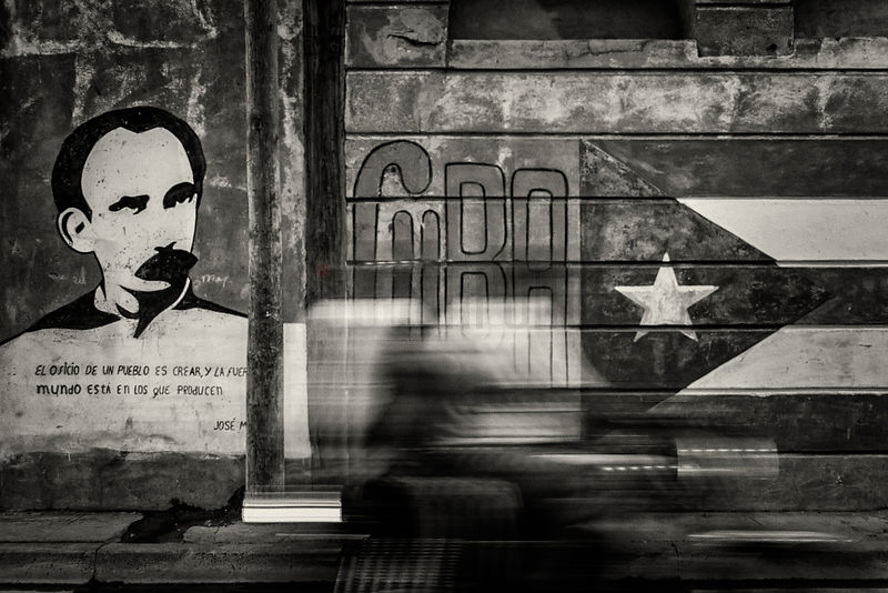 Motorcycle Passing in Front of Cuban Flag Mural