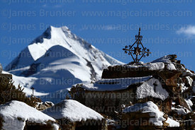 Ornate cross in Milluni cemetery after fresh snowfall and Mt Huayna Potosi, Cordillera Real, Bolivia