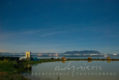 Star filled night sky above tents pitched along a small dam, Riebeck Kasteel mountain and village lights in the distance