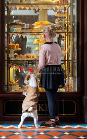 girl and her dog looking in cake shop window