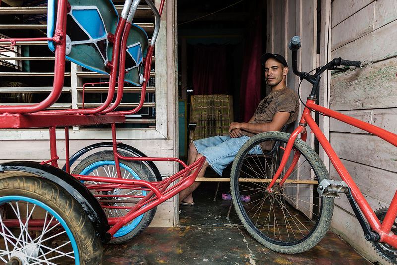 Portrait of a Maqn with his Bicitaxi on the Front Porch