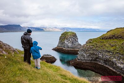 Father and son looking at rugged coastline, Snaefellsnes, Iceland
