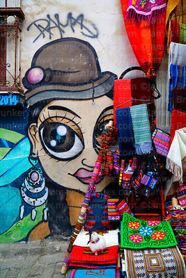 Cholita street art and textiles hanging outside shop in tourist market, La Paz, Bolivia