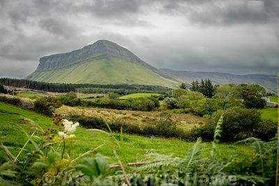 The mighty Benbulbin rock in County Sligo surrounded by green verdant pasture and flowers with a mean and broody sky overhead