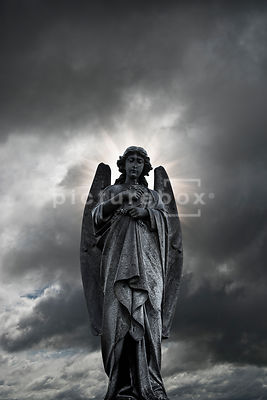 An atmospheric image of a wet angel headstone in a church graveyard, set against a stormy sky.