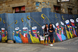 Teenage girls standing next to mural with chunchus dancers painted on corrugated iron fence, Tarija, Bolivia