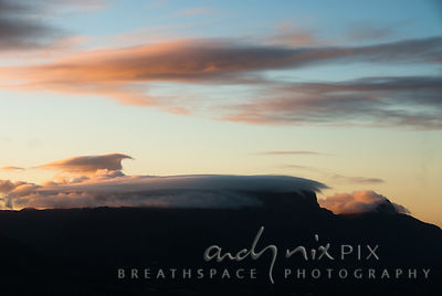 Low cloud lying on the top of Table Mountain and Devil's Peak at sunset, viewed from the south.