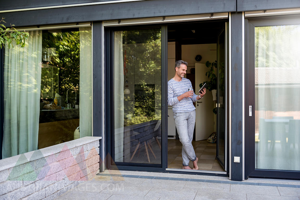 Smiling mature standing at French door at home using a tablet
