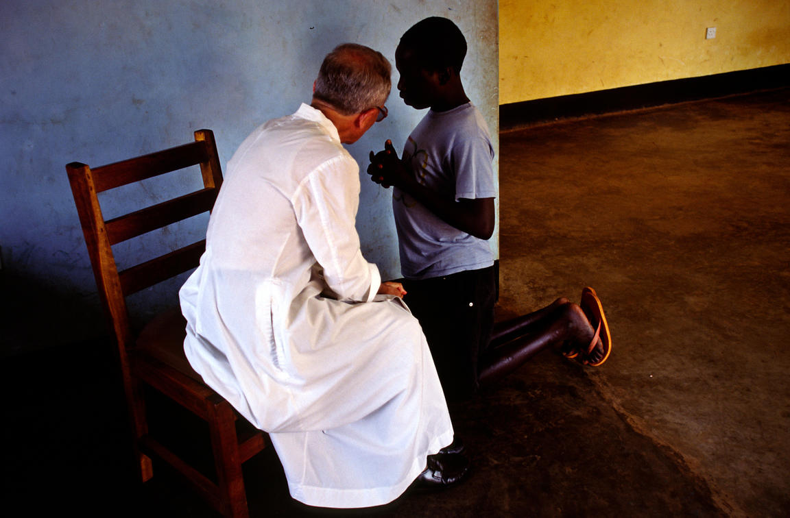 Uganda - Gulu - An Italian priest gives confession to a boy