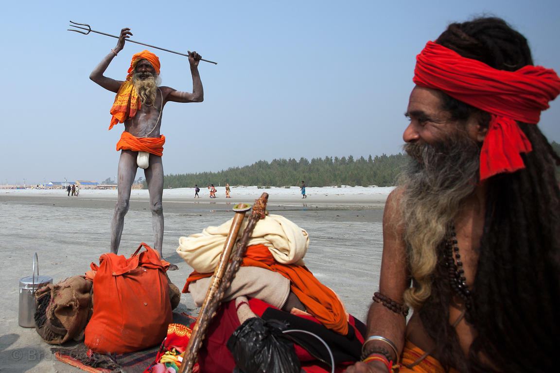 Sadhus (holy men) sit at a camp on the beach at the Gangasagar Mela (festival), a pilgrimage to Sagar Island in India, where ...