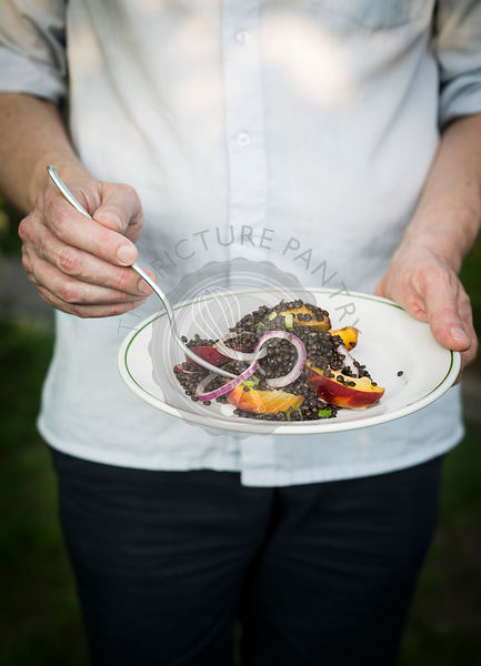 Holding a plate with lentil and fruit salad