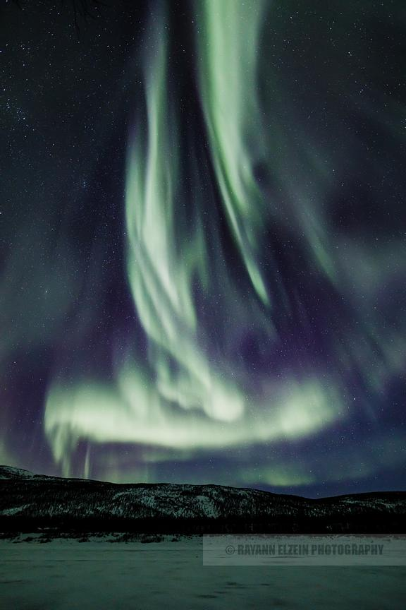 Aurora flaming to the sky above the Teno River, at the border between Norway and Finnish Lapland