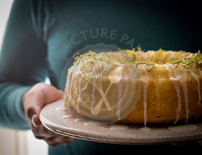 Man holding glazed key lime bundt cake in a ceramic cake plate