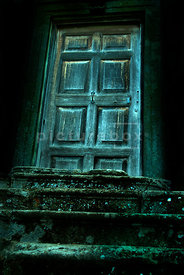 An atmospheric image of a spooky old door at the top of some steps.