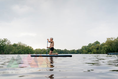 Senior man kneeling on SUP board