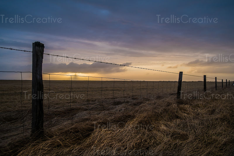 Rays of sunlight shine down from behind clouds during sunset, fence in foreground. Iceland