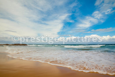Waves Washing across a  Golden Sand Beach with Blue Sky Clouds
