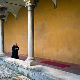 A priest reads as he walks through cloisters in the courtyard of the Saint Augustino Church, Palermo, Italy