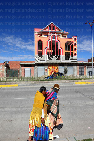 "Aymara women walking past brightly decorated building called a ""cholet"", El Alto, Bolivia"