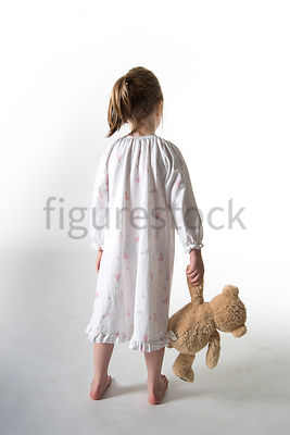 A Figurestock image of a little girl, standing in a night dress holding a teddy bear – shot from eye level.