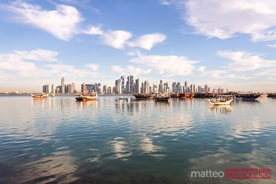 Qatar, Doha. Cityscape with fishing boats in the foreground