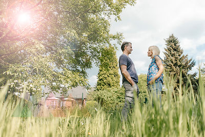 Mature couple standing face to face in garden of their home