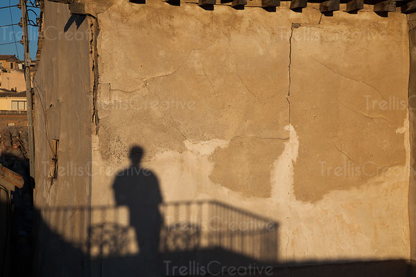 A shadow of a man on an old building at sunset