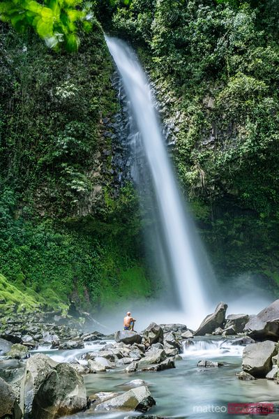 Tourist under waterfall, Arenal, Costa RIca
